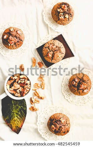 chocolate muffins with pieces of dark chocolate and walnut, light comfortable background, top view,tinting