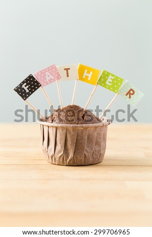 Chocolate muffins with small flag of a word father - stock photo