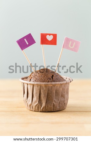 Chocolate muffins with small flag of I Love you - stock photo
