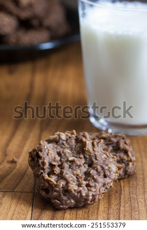 Chocolate no-bake cookies on a table with a glass of milk, illuminated but sunlight coming oin from the right side. - stock photo