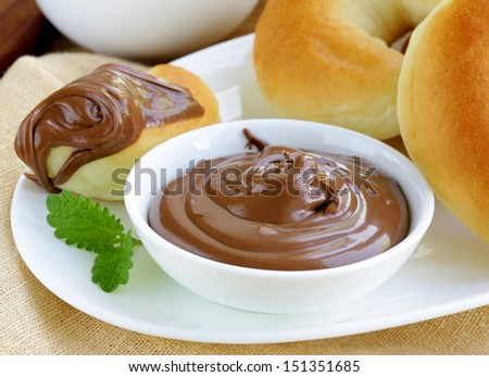 Chocolate nut paste (nutella) for breakfast with bread rolls - stock photo