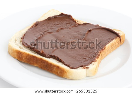 Chocolate nut spread on sliced white bread on plate. - stock photo