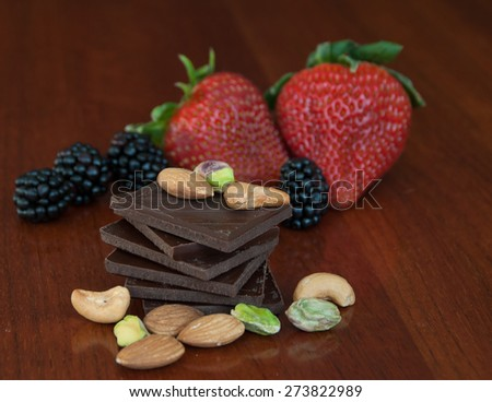 Chocolate, nuts and berries  on glossy wooden background - stock photo