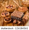 Chocolate, nuts and spices on a brown table - stock photo