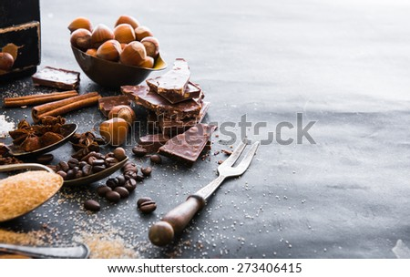 Chocolate, nuts, spices in the spoons on the table dark - stock photo
