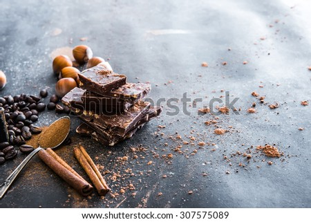 Chocolate, nuts, spices on a smooth black table - stock photo
