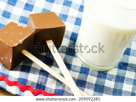 Chocolate on wooden stick and a glass of milk.