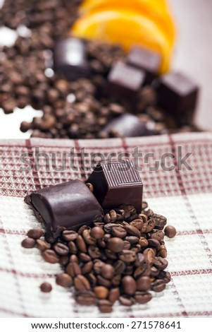 Chocolate, orange and coffee beans on wooden table - stock photo