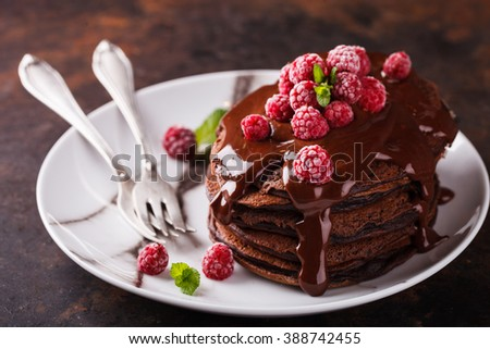 Chocolate pancake with chocolate glaze,raspberries and mint.selective focus - stock photo