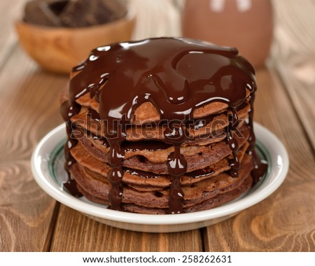 Chocolate pancakes on a brown background