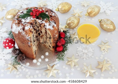 Chocolate panettone christmas cake with holly and egg nog and gold and white bauble decorations.