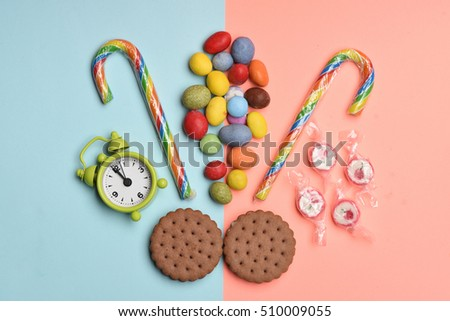 Chocolate pastry, colorful dragee with raisins or peanuts inside, striped caramel candies, sugar candies and green alarm clock on colorful background