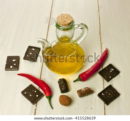 Chocolate pieces and bonbons with unusual chocolate components: sea salt flakes, red hot chilli peppers, and olive oil in a pitcher, on a light wooden background texture, with copyspace - stock photo