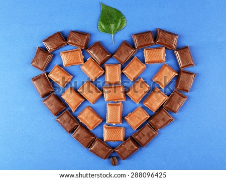 Chocolate pieces arranged in heart shape with green leaf on blue background - stock photo
