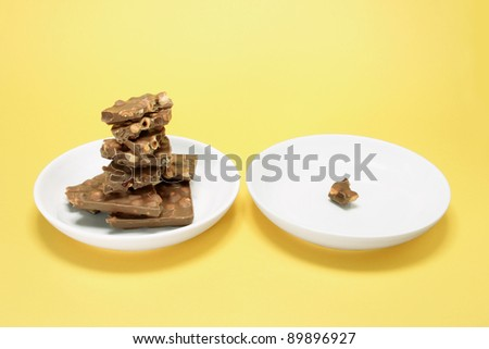 Chocolate Pieces on Plate with Yellow Background - stock photo