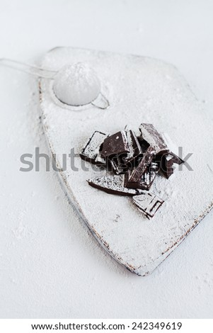 Chocolate pieces on white wooden background. Selective focus. Rustic style.  - stock photo