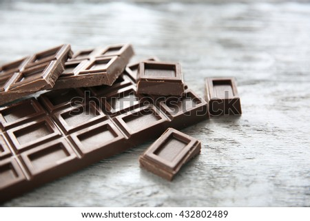 Chocolate pieces on wooden background - stock photo