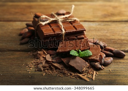 Chocolate pieces, shavings and cocoa beans on color wooden background - stock photo