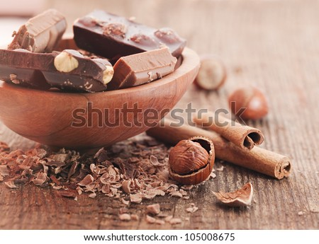 Chocolate pieces   with cinnamon stick and hazelnut  on wooden background