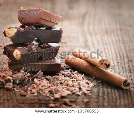 Chocolate pieces  with cinnamon stick on wooden background - stock photo