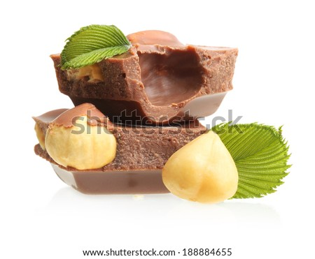 Chocolate pieces with hazelnuts on white background