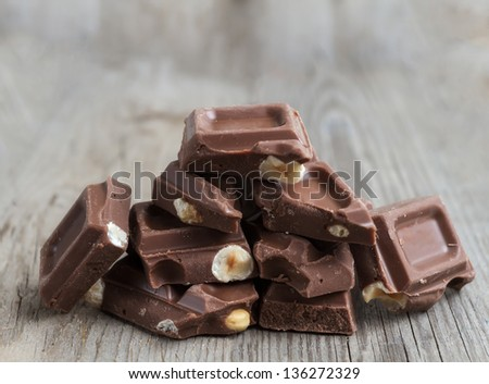 Chocolate pieces with nuts on wooden background - stock photo