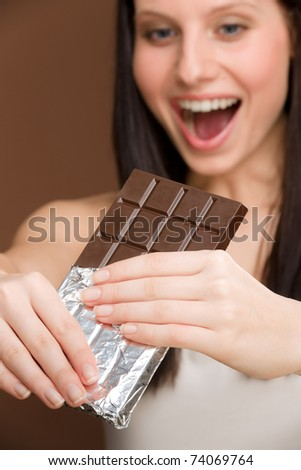 Chocolate - portrait of young woman bite off sweets
