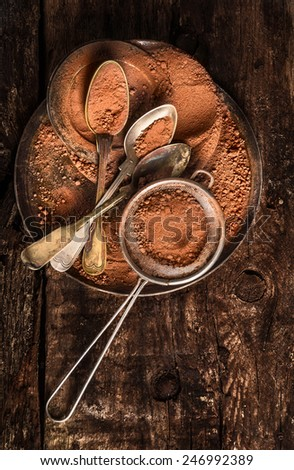 Chocolate powder with spoons and strainer on dark wooden background, top view - stock photo