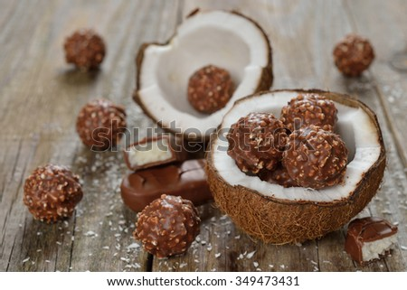 Chocolate praline and coconut on a wooden background - stock photo