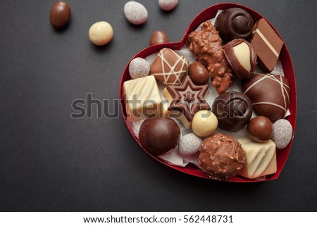 Chocolate pralines in red heart shape box on black background
