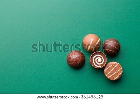 chocolate pralines on a green chalkboard - stock photo