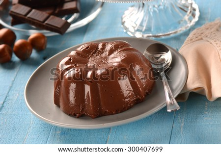 chocolate pudding with ingredients around on the table blue - stock photo