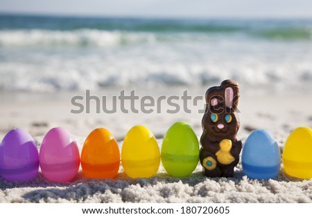 Chocolate Rabbit and easter eggs on ocean beach  - stock photo