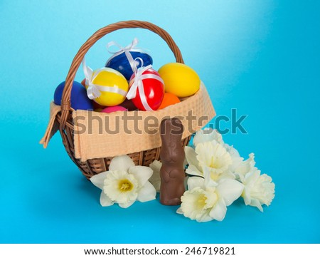 Chocolate rabbit, white narcissuses and a basket with eggs, on the blue - stock photo