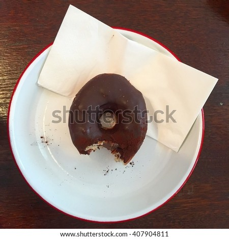 Chocolate ring donut with a bite - stock photo