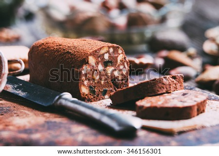 Chocolate salami with biscuits on a wooden board, with ingredients.