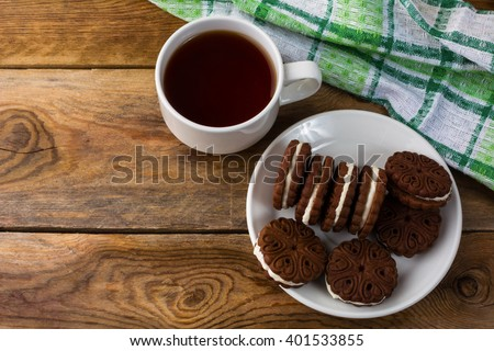 Chocolate sandwiches and tea cup, top view. Sweet dessert. Homemade biscuit. Cookies sandwiches and cup of tea. Breakfast cookie.