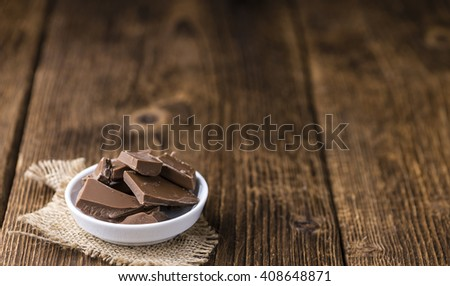Chocolate (selective focus) on an old wooden table (close-up shot) - stock photo