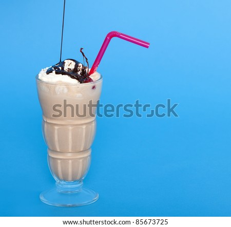 Chocolate shake with a drizzle of chocolate sauce on a blue background - stock photo