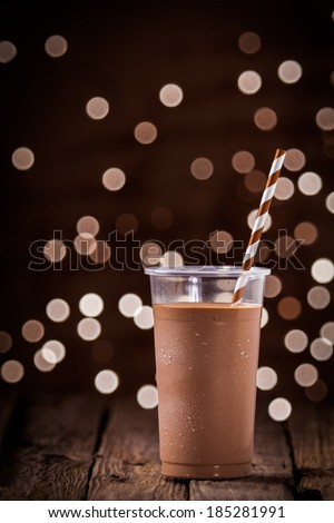 Chocolate smoothie or milkshake with a sparkling bokeh of party lights in the background standing on a rustic wooden table at a restaurant or bar - stock photo