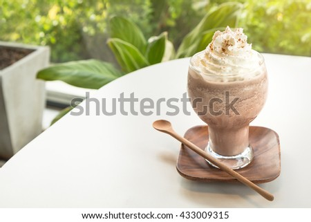 Chocolate smoothies (Cocoa blended) topped with whipped cream and cocoa powder in glass cup on white table. Wooden saucer and spoon. Interior coffee shop. - stock photo