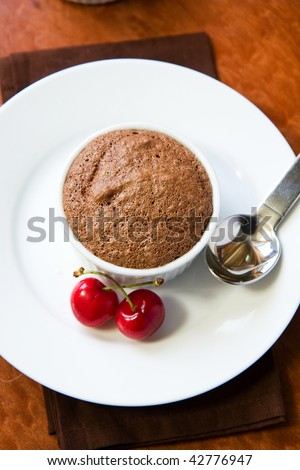 Chocolate souffles in ramekins garnished with cherries