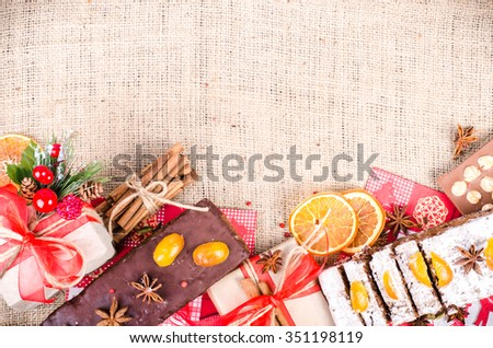 Chocolate spices cake, star anise and dried fruits, packed gifts with red tapes on sackcloth, canvas. Sweet frame. Free space for your text.