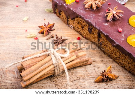 Chocolate spices cake with star anise and dried fruits, cinnamon, cloves, cardamom on wooden background. Christmas gift. - stock photo