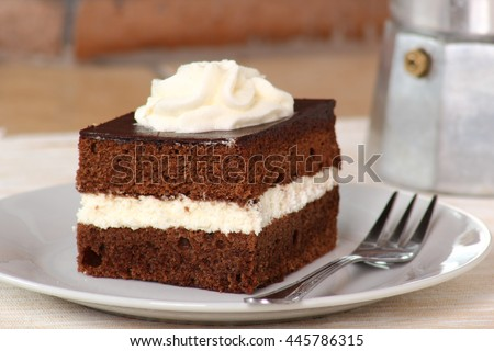 Chocolate Sponge Cake filled with whipped cream on white plate with fork at moka pot background