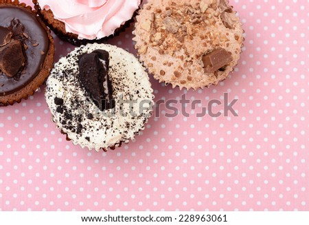 Chocolate Strawberry Cookies and cream cup cake on vintage pink table cloth - stock photo