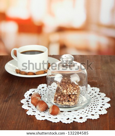 Chocolate sweets under glass cover and hot drink on bright background - stock photo