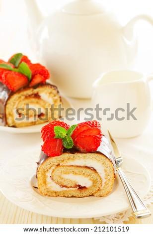 Chocolate swiss roll cake with strawberries - stock photo