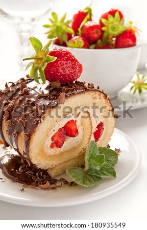 Chocolate swiss roll cake with strawberries on the white background - stock photo