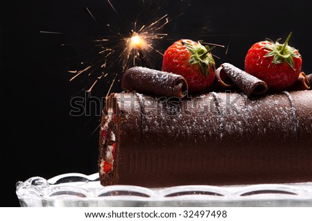 Chocolate swiss roll with strawberries and sparkler decoration - stock photo